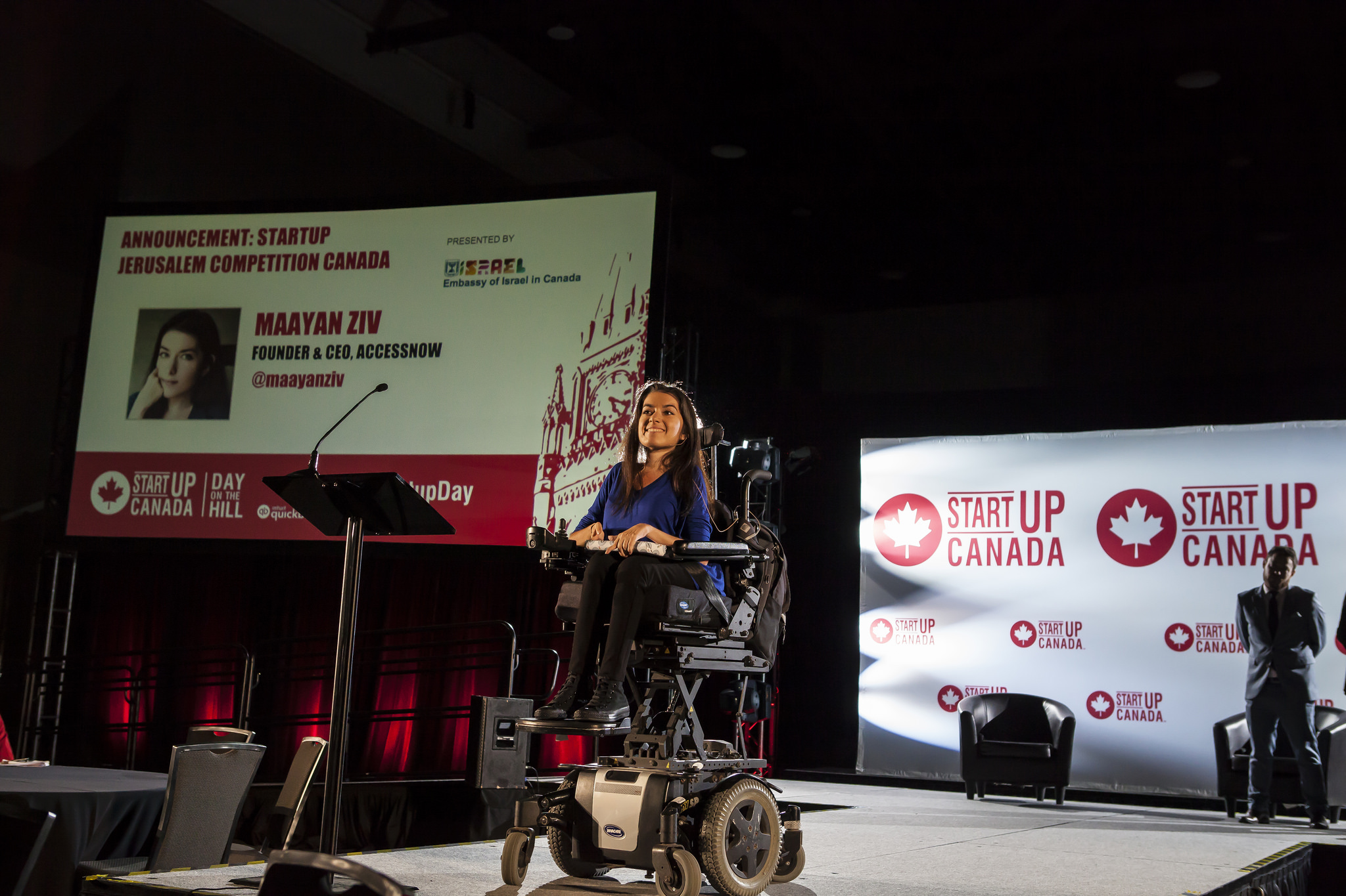 "maayan smiles on stage at the startup canada day on the hill event. behind her is a large screen that reads ""Announcement: Startup Jerusalem Competition Canada"" in red"