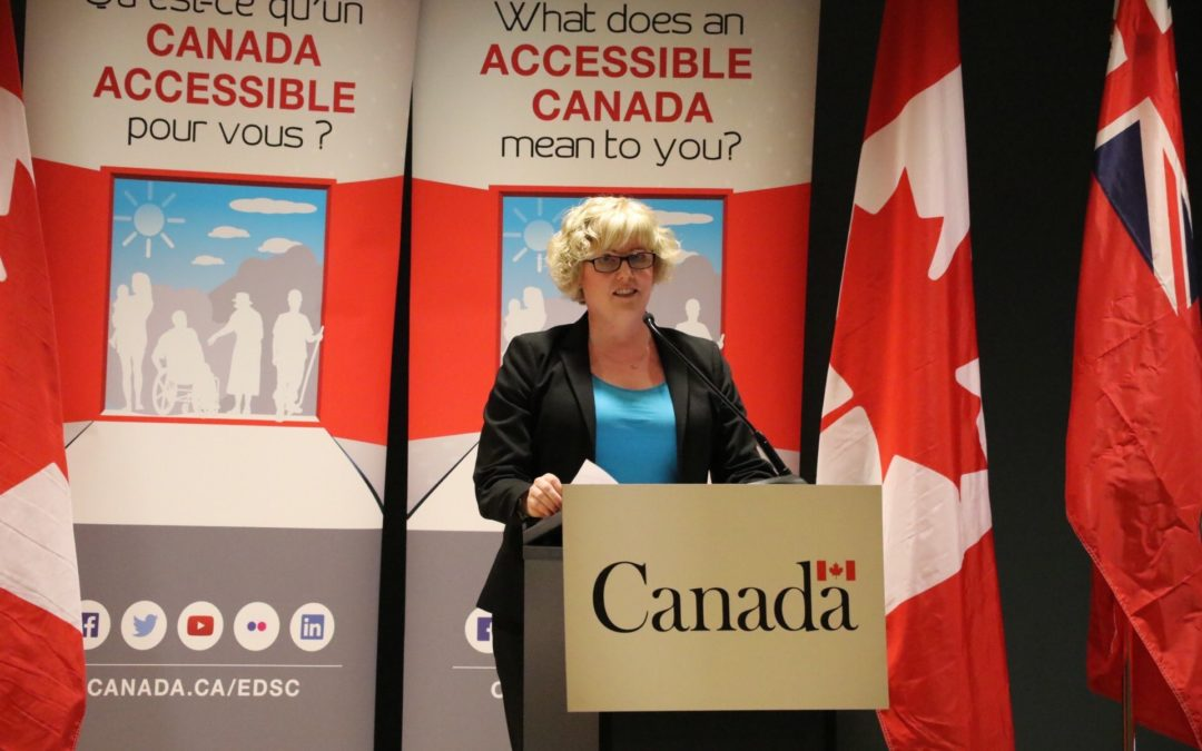 The Hon. Carla Qualtrough stands at a podium branded with the Government of Canada logo in front of Canadian flags at Abilities Centre.