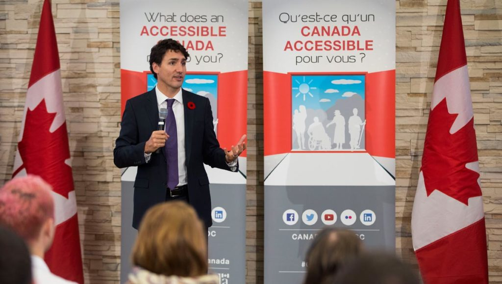 Justin Trudeau delivers address in front of accessible canada banners