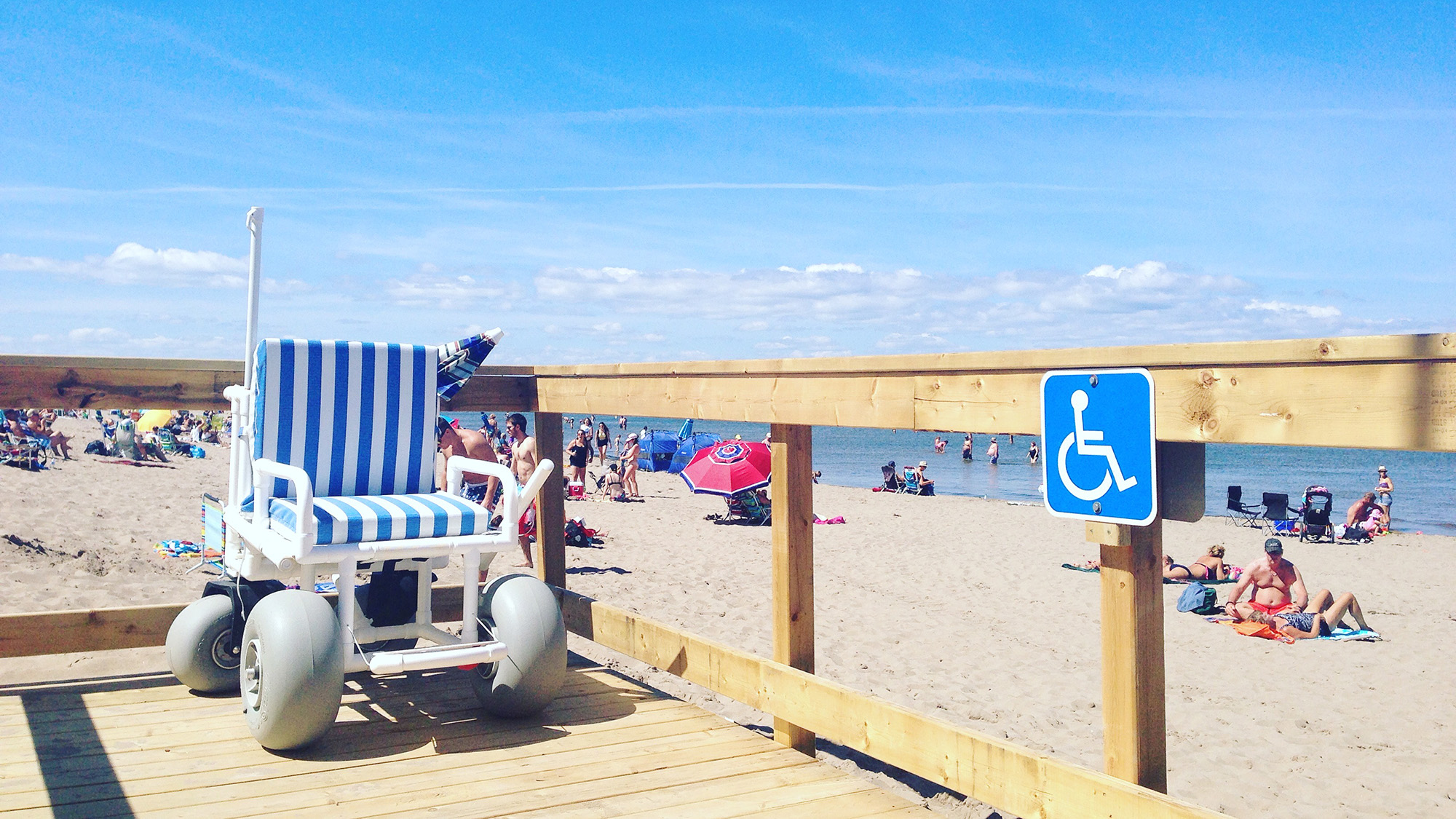 beach wheelchair sits on boardwalk with the beach in the background
