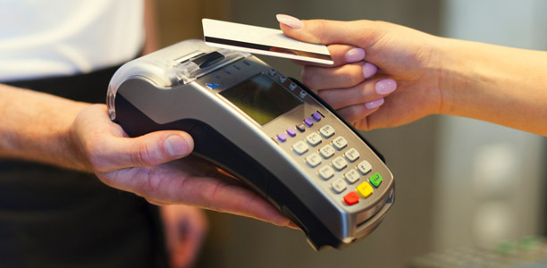 hand tapping a credit card on a payment machine