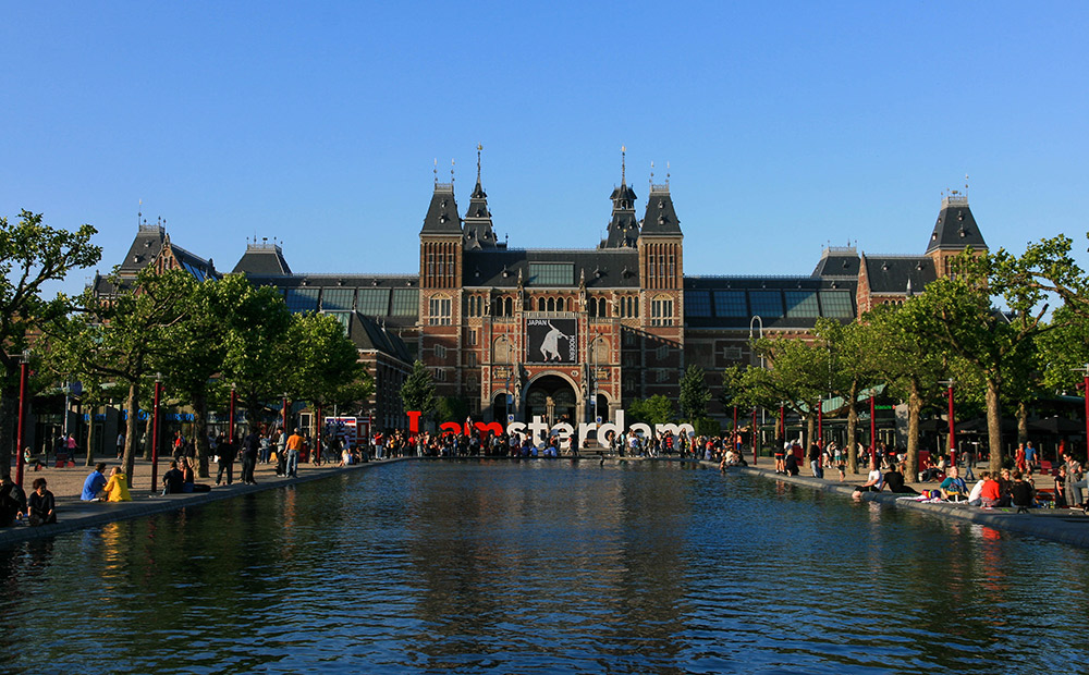 exterior of rijksmuseum on the water, trees lining each side