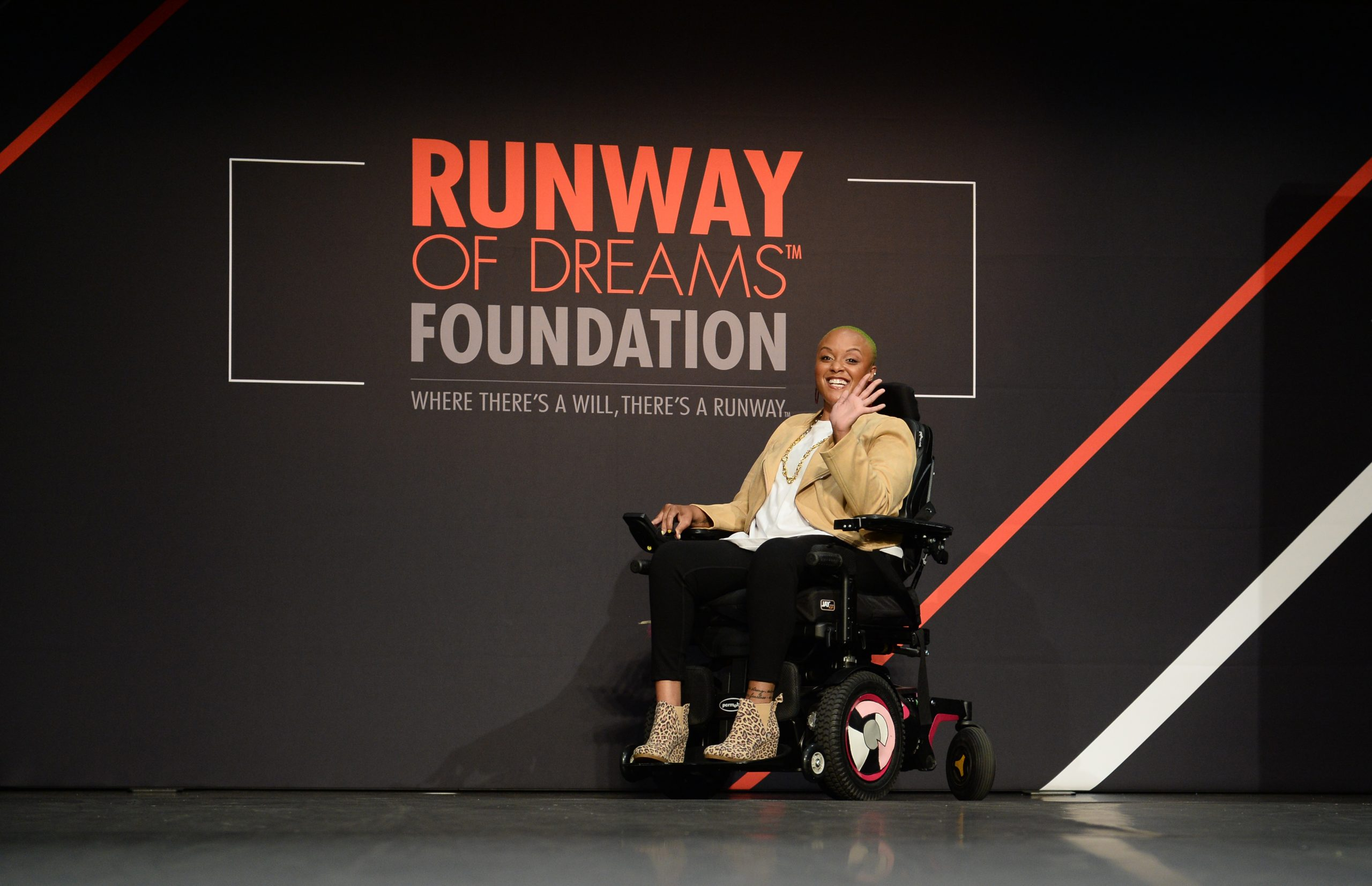 "Keisha in a wheelchair in the middle of a fashion runway. She is waving and smiling at the camera. There is a black backdrop behind her that says ""Runway of Dreams Foundation: Where there's a will, there's a runway."""