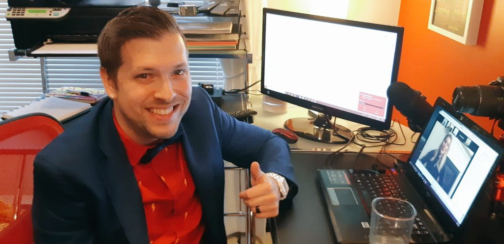 Marco dressed up formally with a suit and a bowtie. He is looking at the camera, smiling and giving a thumbs up. He is at home, in his office and surrounded by computer screens.