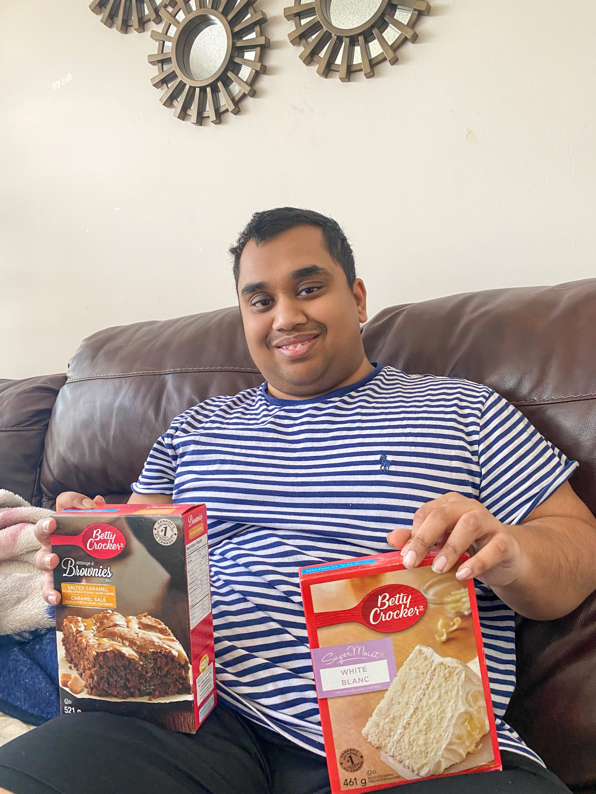Ridwan sitting on a couch and smiling at the camera. He is holding boxes of Betty Crocker baking mixes. One hand has a brownie mix and the other a cake mix.