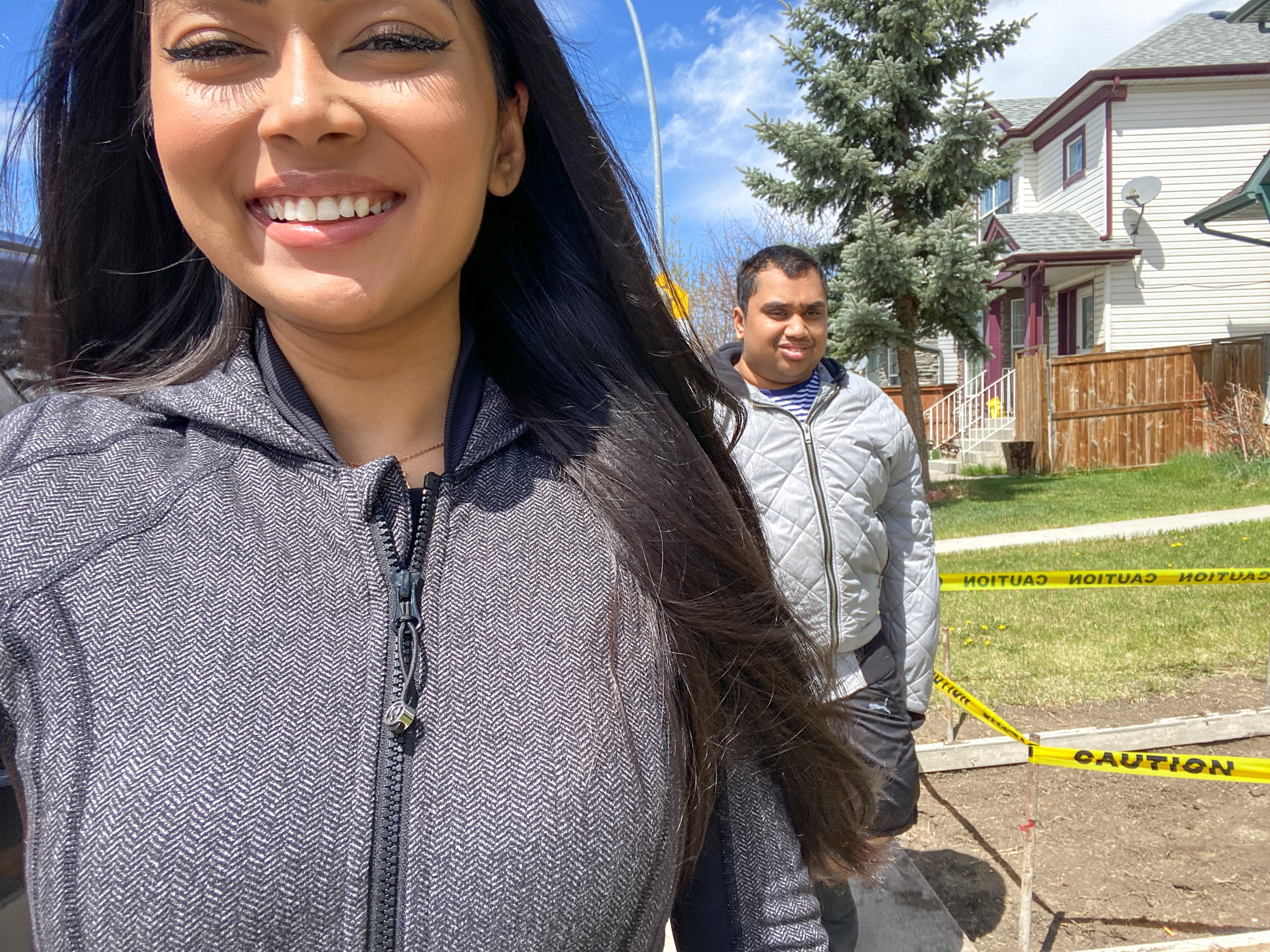 A selfie of Naz and her brother Ridwan during one of their outdoor walks. It is a beautiful day with blue skies and Naz is smiling.