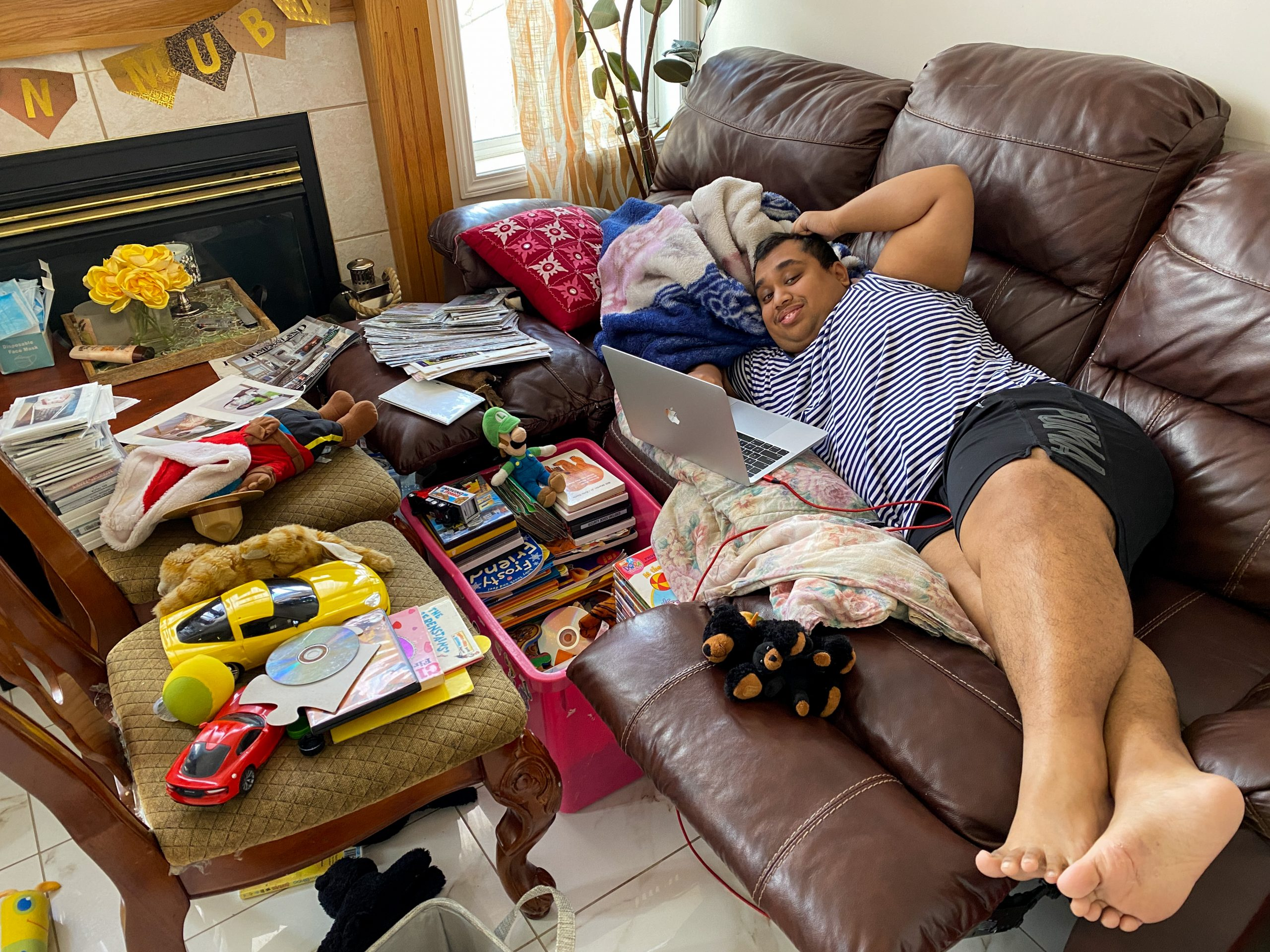 Ridwan lying down on the couch with the laptop on front of him