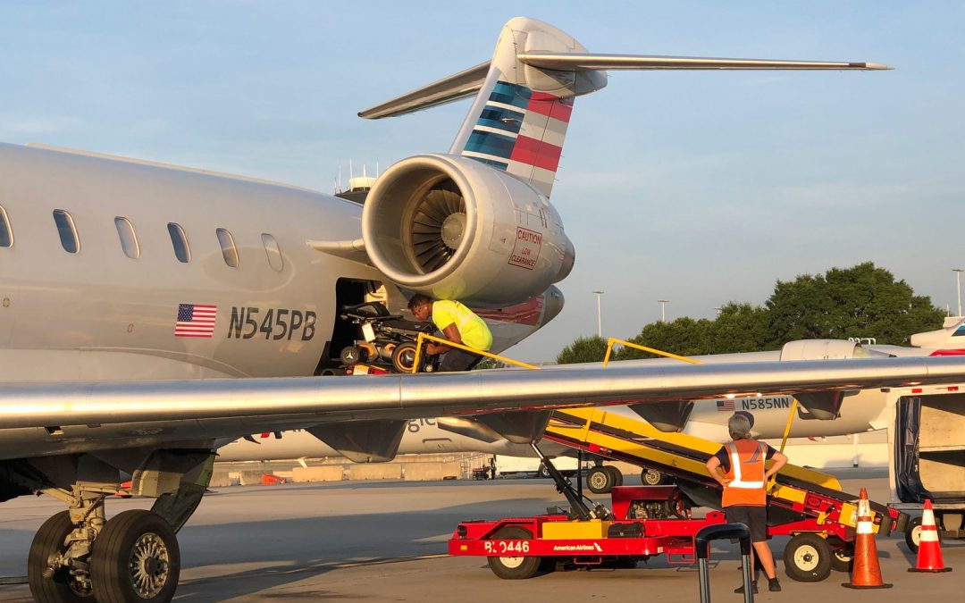 a wheelchair is being loaded into the belly of an airplane via long ramp