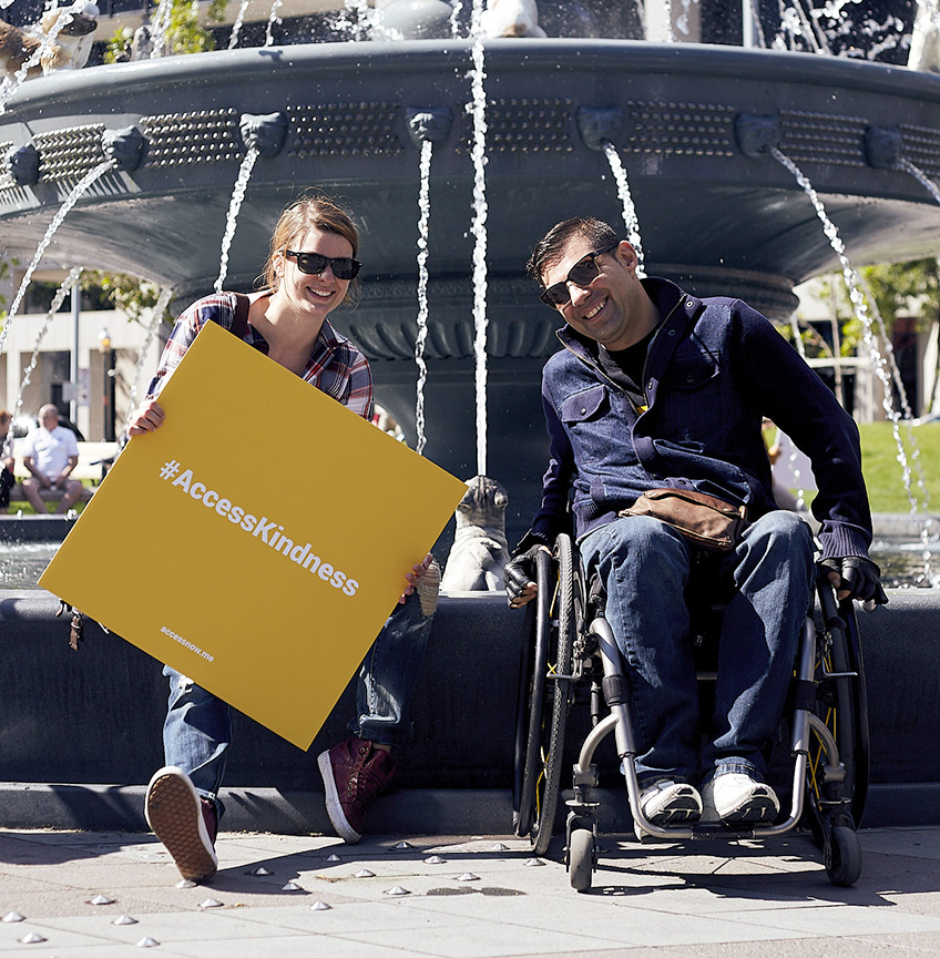 two people smiling, one using a wheelchair, one doesnt