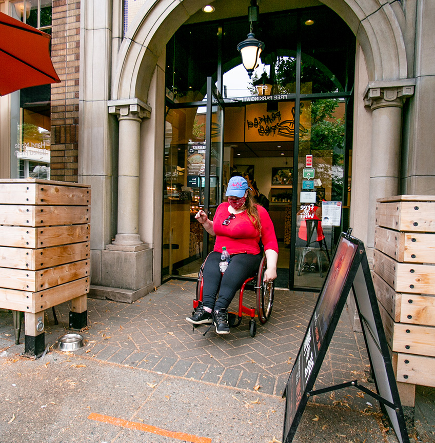 woman in a wheelchair exiting a store